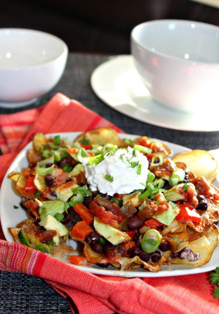 veggie potato nachos on a  white plate with salsa and sour cream