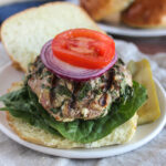 Spinach and feta turkey burger on a roll topped with onions and tomatoes