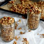 granola in two jars with a sheet pan in the background