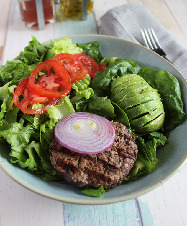 a bowl filled with lettuce tomatoes onions avocado and a burger