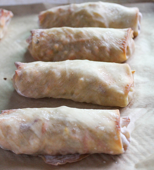 baked stuffed egg rolls lined up on a baking sheet