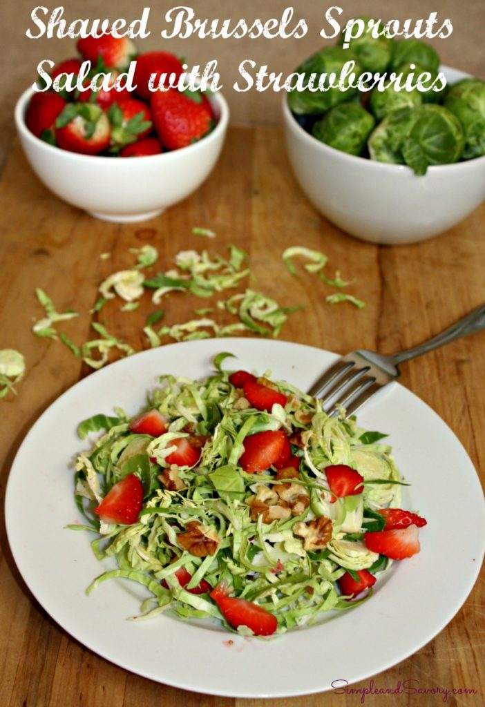 salad on a plate with a bowl of strawberries and blue berries in the background