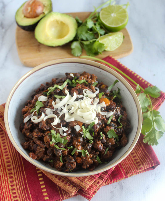 Bison chili in a bowl with cheese and cilantro on top