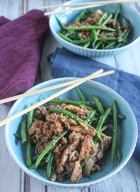 green beans and pork stiry fry in a bowl with chop sticks