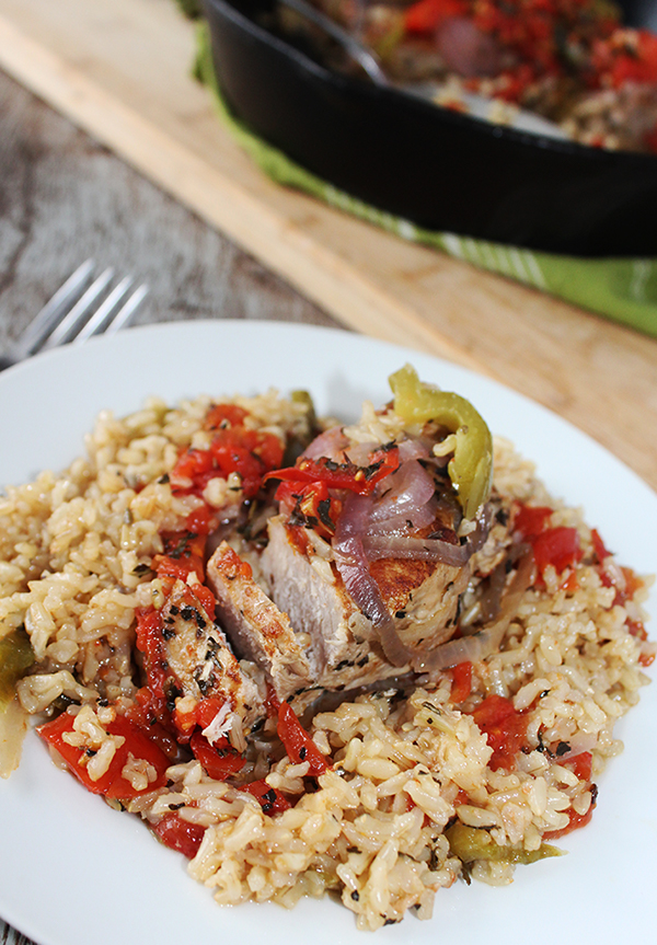 a boneless pork chop topped with tomatoes, peppers and onions over rice on a white plate