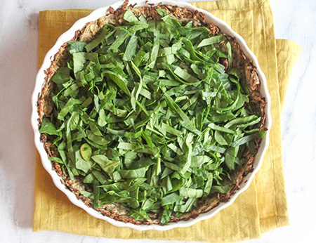 spinach in quiche crust on a table