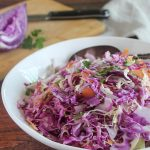 a close up of coleslaw in a bowl with a spoon