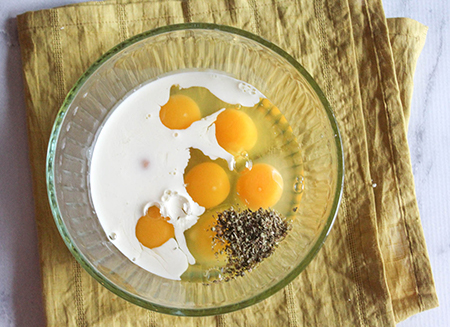 eggs, milk and oregano in a bowl