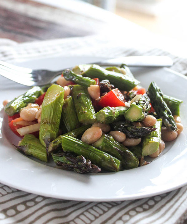A close up view of grilled asparagus salad in a bowl