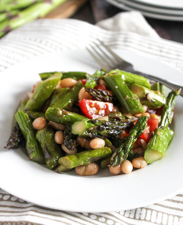 Grilled asparagus salad in a bowl with tomatoes and white beans