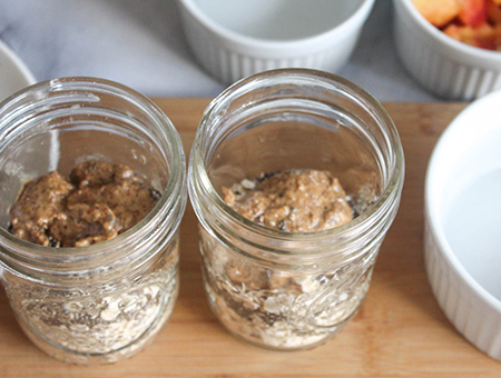 two 8 ounce mason jars with oats, chia seeds and almond butter