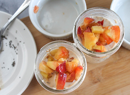 two small jars of oatmeal topped with chopped peaches