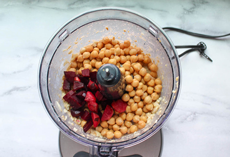 Beets and check peas in a food processor bowl