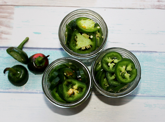 On overhead view of pickled jalapeno slices in three jars with three jalapeno stems on the side.