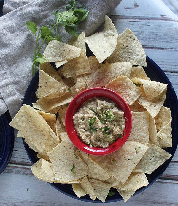 Vegan queso dip in a red bowl with chips on a blue plate with cilantro on the side