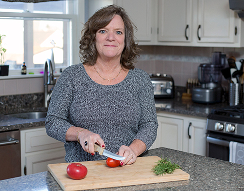 A picture of Anne cutting tomatoes in her kitchen