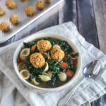 Tuscan vegetable Soup with white bean balls in a bowl with a spoon
