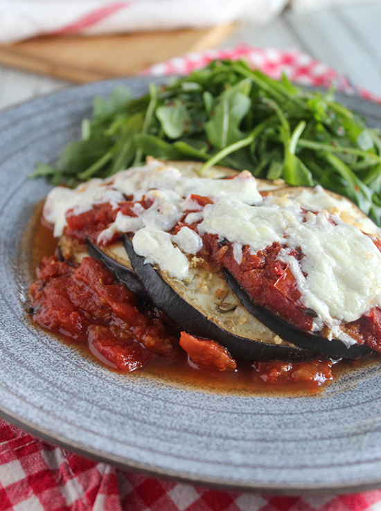 a close-up shot of eggplant parmesan on a blue plate with arugula