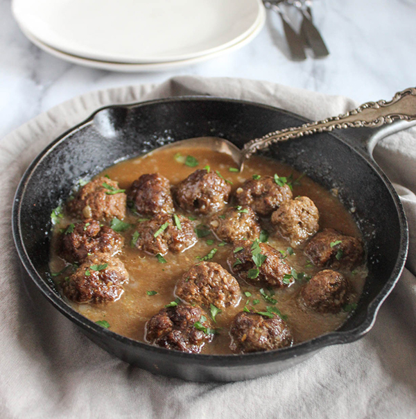 meatballs in brown gravy in a cast iron skillet with a spoon