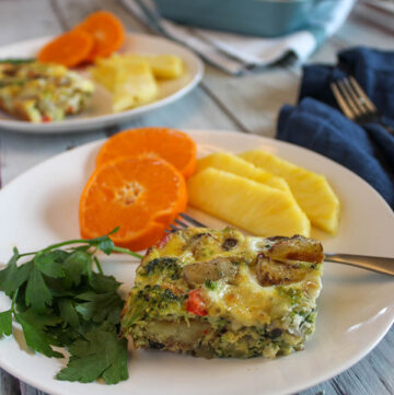 Vegetable breakfast casserole on a late with fruit and a fork