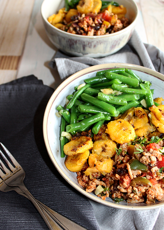 Fried plantains and green beans in a bowl with chicken picadillo