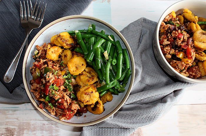 spciy chicken picadillo in a bowl with plantains