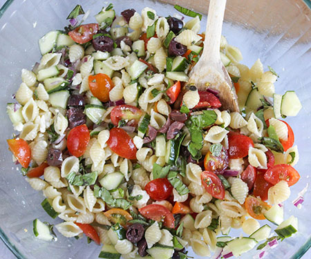 Pasta salad with a wooden spoon in a mixing bowl