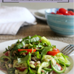 spiralized cumber salad with tomatoes on plate with a fork