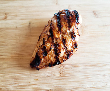 Cooked chicken breast on a cutting board