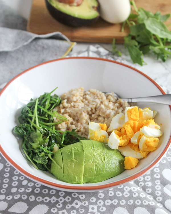 healthy savory breakfast bowl with sauteed greens oats eggs and avocado in a bowl