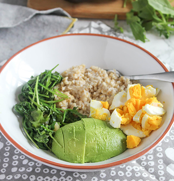 savory breakfast bowl filled with avocado, sauteed greens, whole grains and a hard boiled egg.