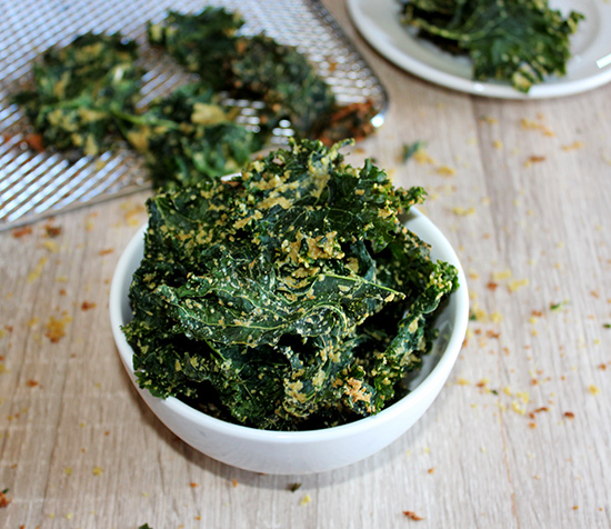 Air Fryer kale chips in a white bowl with a tray in the background
