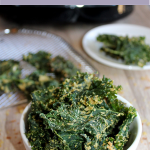 kale chips in a bowl and a plate of chips in the background