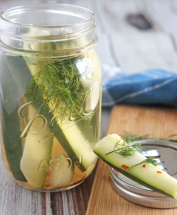 zucchini refrigerator pickle on a fork with a jar behind it