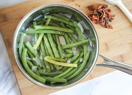 onions and green beans in a pan cooked
