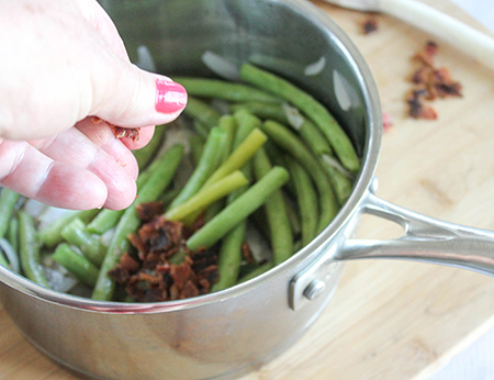 green beans in pan with bacon crubmles being added by hand