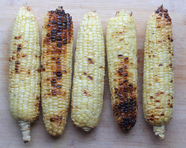 charred grilled corn on a cutting board