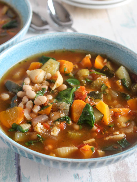 vegetable minestrone soup close up in a blue bowl