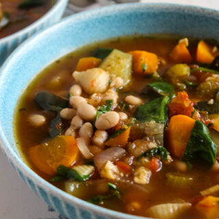 vegetable minestrone soup up close in a blue bowl