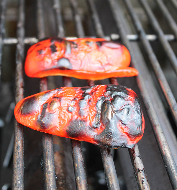 red bell peppers on the grill with charred skin