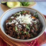 bison chili topped with cheese and cilantro in a bowl