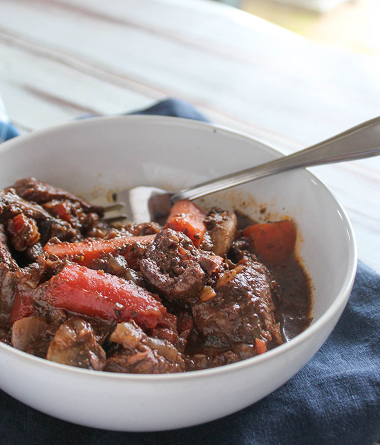 a close up view of beef stew in a white bowl with a fork