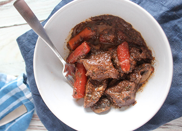 Overhead of beef stew in a white bowl with a fork