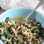 Sausage and Kale soup in a bowl with a spoon