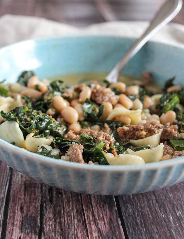 a close up picture of sausage and kale soup in a bowl