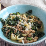 sausage and kale soup in a bowl topped with cheese