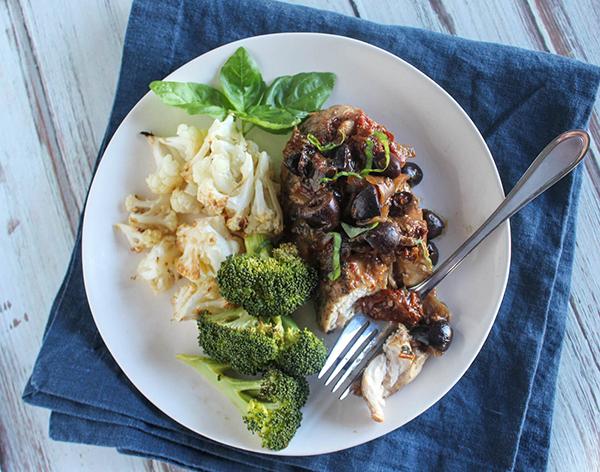 Mediterranean chicken on a plat with broccoli and cauliflower