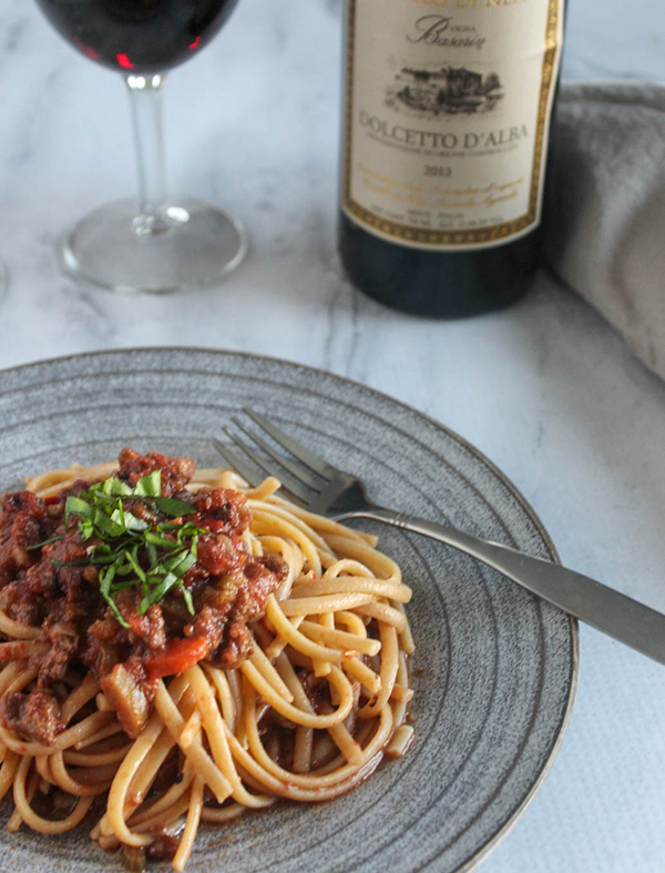 bolognese sauce on a plate with a fork and wine in the background