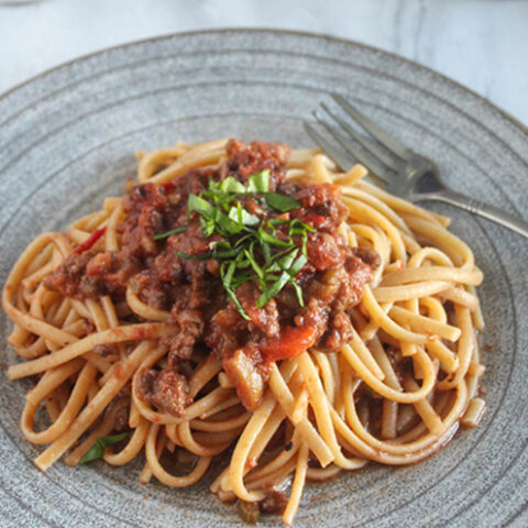 spaghetti covered with bolognese sauce and basil ribbons on top