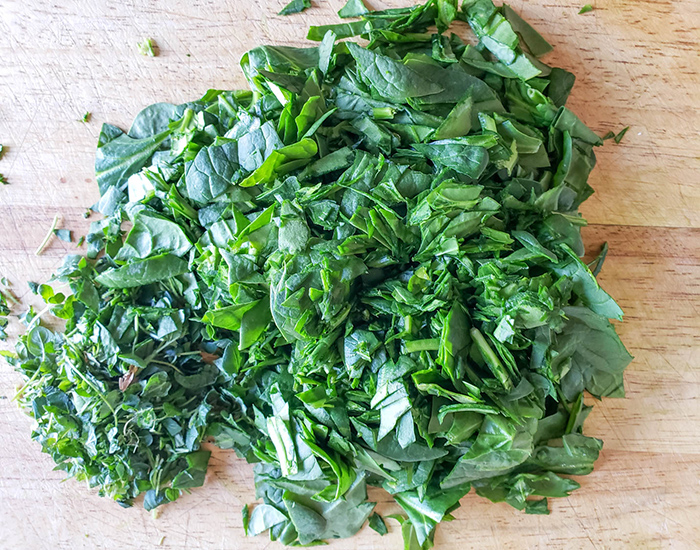 an overhead view of chopped spinach and oregano